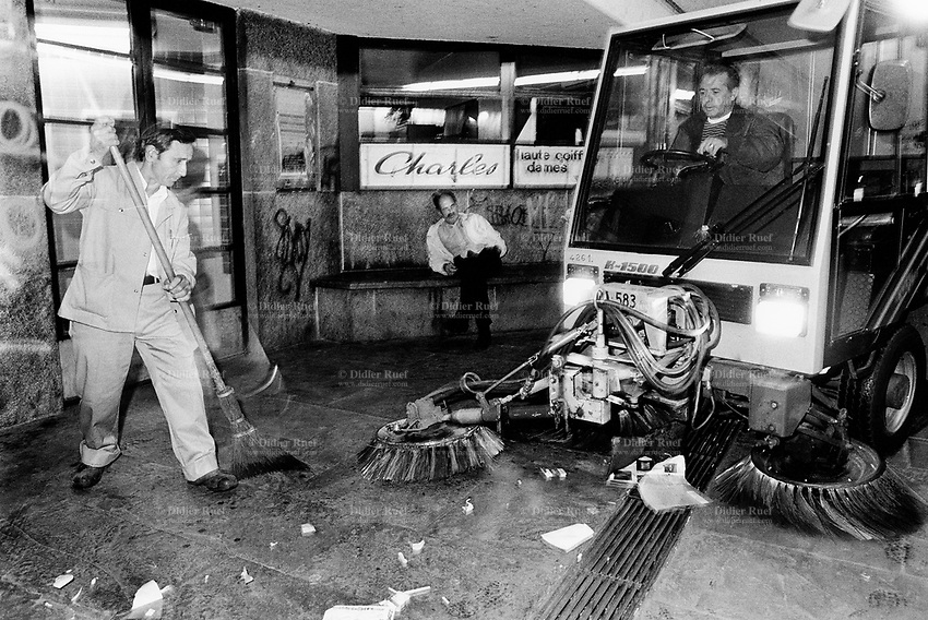 Switzerland. Geneva. Garbage collectors. Streets cleaning.  A street sweeper with his broom, another worker driving a street brooming machine, both men are cleaning the street in the early morning. A man seated on a bech sleeps. Night time. © 1991 Didier Ruef