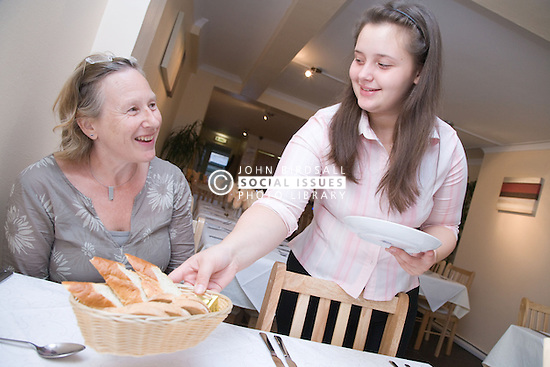 Waitress serving customer with bread at a Polish restaurant,