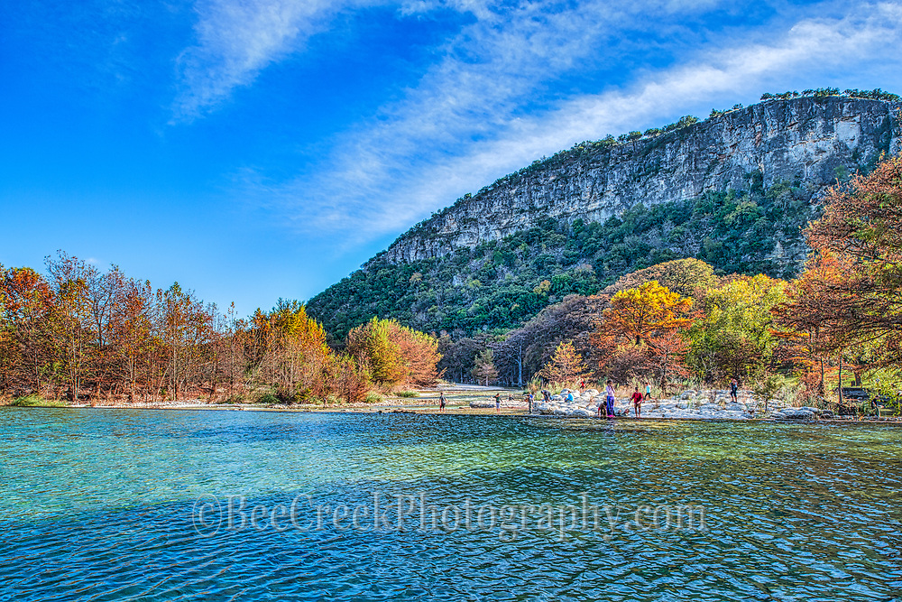 Garner State Park Old Baldy Peak during the fall season as the Frio River flows over the dam down toward Con Can with the fall colors of the trees