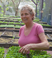mature woman enjoying time in a greenhouse filled with plants