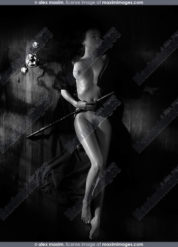 Beautiful nude woman with a bamboo flute wearing a kimono lying on the floor in dim dramatic light view from above Black and white