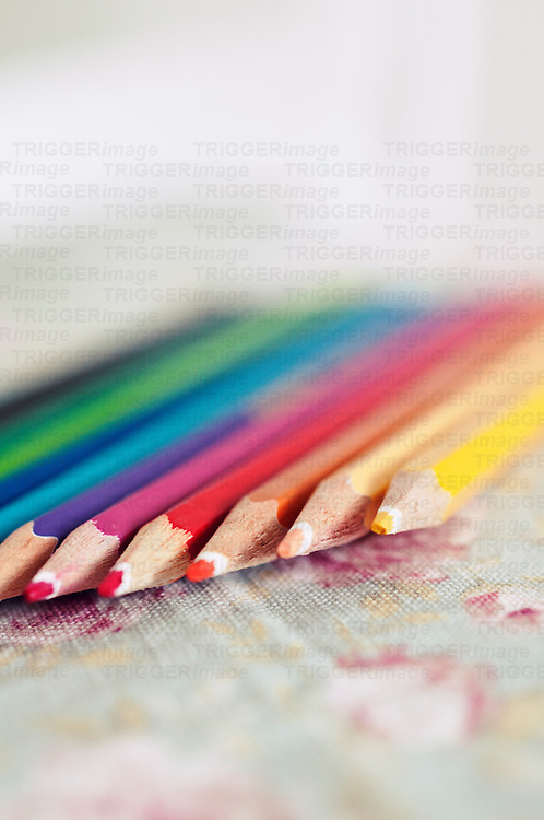 A collection of rainbow coloured pencils in a line