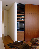 A walnut-faced sliding door conceals the entertainment system in the living room