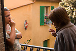 Taking a smoke break on the balcony of the house are Daniela Ciolfi, wife of Fabio Pellegrini and translator Jennifer Zaid of Philadelphia and Rome. Revisit with the Pellegrini family, 2005, Pienza, Italy. The Pellegrinis were Italy's participants in Material World: A Global Family Portrait, 1994 (pages: 198-199), for which they took all of their possessions out of their house for a family-and-possessions-portrait. In 1996, UNESCO declared the town a World Heritage Site.