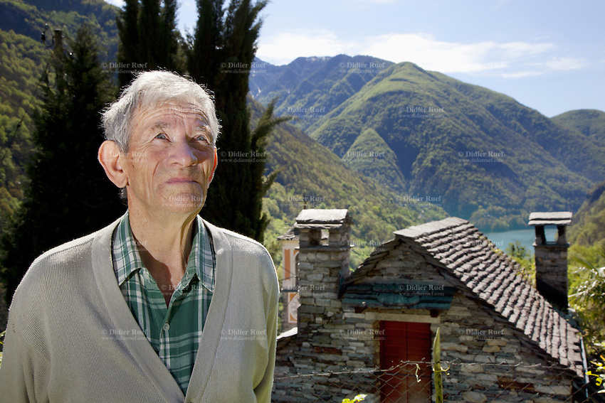 Switzerland. Canton Ticino. Corippo lies in the Verzasca valley. Guglielmo Scettrini stands in his garden. The stone houses are built from the local Ticino granite with stone roofs and have changed little for several hundred years. With a population of just 16, Corippo is the smallest municipality in Switzerland. Despite this, it possesses the trappings of communities many times its size such as its own coat of arms and a town council consisting of three local citizens. A town council is a democratically elected form of government for small municipalities. A council may serve as both the representative and executive branch. The village has maintained its status as an independent entity since its incorporation in 1822. 8.05.13 © 2013 Didier Ruef