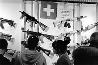 Switzerland. Canton Luzern. Luzern. Swiss gun show. The international gun show is a fair for hunting and sporting weapons, but also for small arms, handguns and machine guns. It takes place once a year in Luzern. A meeting point for exhibitors, customers and collectors, in order to buy or sell modern and old weapons. On the Glaner Waffen Manufaktur&rsquo;s stall, visitors are looking stall at various semi-automatic sub-machine guns from Windham Weaponry AR-15. An assault rifle is a selective-fire rifle that uses an intermediate cartridge and a detachable magazine. A swiss flag is wall. Windham Weaponry is of the finest firearms manufacturers in the U.S.A. which brings to market the highest quality AR type rifle possible. The flag of Switzerland consists of a red flag with a white cross (a bold, equilateral cross) in the centre. It is one of only two square sovereign-state flags.<br /> 25.03.2017 &copy; 2017 Didier Ruef
