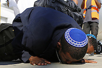 New Jewish immigrants kiss the ground during a welcoming ceremony after arriving on a flight from Ethiopia, August 28, 2013 at Ben Gurion airport near Tel Aviv, Israel. Over 400 Ethiopian Jews arrived on the flight to Tel Aviv, the last of a series of monthly flights that were part of Operation Dove's Wings, an Israeli government initiative to bring to Israel the remainder of the Falash Mura, members of the Ethiopian Jewish community whose ancestors converted to Christianity during the 19th and 20th century.  Photo by Oren Nahshon
