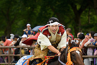 Racing on horse, Somanomaoi Festival, Minami-soma City, Fukushima Prefecture, Japan, July 27, 2013. During the four-day-long Somanomaoi Festival members of old samurai families ride horseback through the town in traditional armour.  They also take conduct ceremonies at local shrines, take part in horse races, and compete on horseback to catch a flag launched into the air by fireworks.