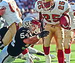 Oakland Raiders vs. San Francisco 49ers at Oakland Alameda County Coliseum Monday, August 30, 1999.  49ers beat Raiders  16-8 in a preseason game.  Oakland Raiders linebacker Greg Biekert (54) tackles San Francisco 49ers running back Charlie Garner (25).