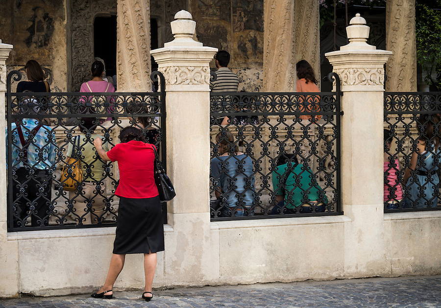 BUCHAREST, ROMANIA - September 30, 2012: Woman outside a church during Sunday service in Romania