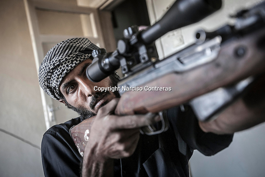 An FSA sniper watchs over the enemy position at the first line of fire in Karmal Jabl neighborhood, district of Arkup, at the northeast of Aleppo CIty.