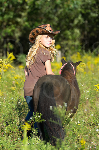 Girl walking miniature horse through summer goldenrod field in late afternoon, blonde with cowboy hat, Pennsylvania, PA, USA.