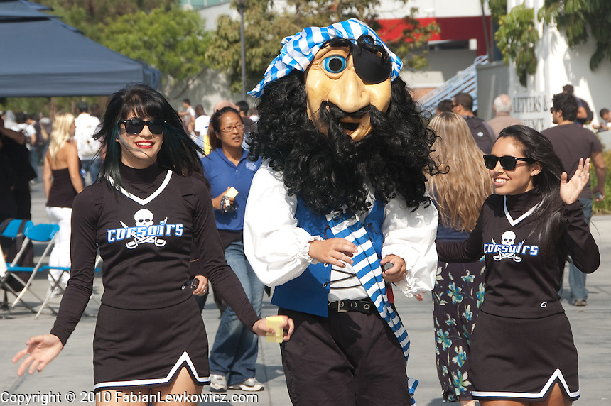 Santa Monica College mascot, Pico the Pirate, with cheerleaders Byanca Reynosa, 22, (left) and  Xochitl Lyndon 19, walk through the SMC Quad on Tuesday while promoting their homecoming football game. .The SMC Corsairs will take on LA Southwest Cougars at Corsair Field on Saturday, October 16, at 6pm..There will be Corsair Giveaway during halftime, including an Acer Computer and a Pirate Costume Contest. The winner receives an Apple iPad with Wi-Fi - 16 GB!  Winner will be determined at halftime by the audience. First 300 coming to the game will get a free Grilled Cheese Truck sandwich! Culver City Centaur Band will be performing!