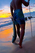 Local fisherman with his catch returning from the sea at dusk, Ka'anapali, Maui