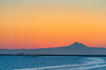 The sun prepares rises behind Mt. Baker on the mainland, with the Dungeness Spit lighthouse in the foreground.