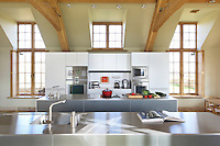 The kitchen units are of dark grey anodised aluminium topped with stainless steel work tops
