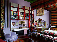 The Moroccan-influenced guest bedroom is dominated by a four-poster bed and has a free-standing bath beneath the bookcase