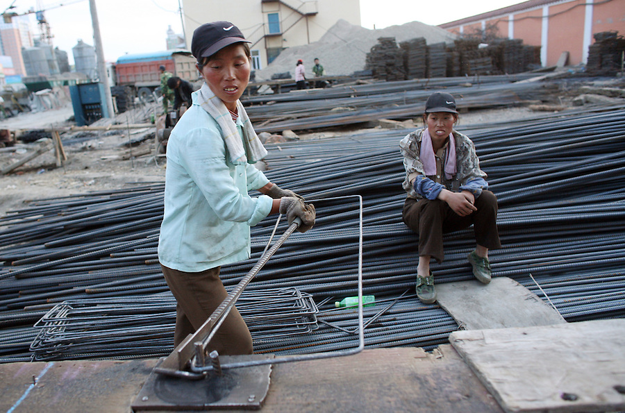 Women workers shape bars of steel in Mudanjiang in China's northern Heilongjiang province July 4, 2006. The government is seeking to avoid a sudden economic slowdown in the world's biggest market for steel and second-largest oil user by shifting its focus to raising incomes and consumer spending.
