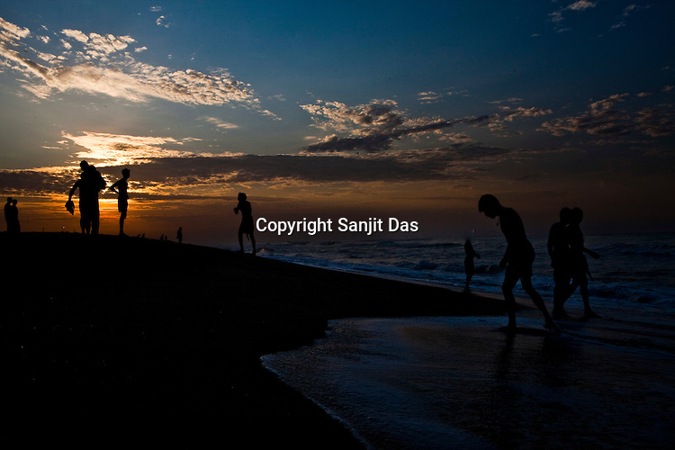 Tourists seen returning to the beach after taking an early morning bath in Bay of Bengal in Puri, Orissa, India. A dip in its salty waters is believed to hold great religious significance, as a result these golden sand beaches sees is a never-ending rush of pilgrims and tourists. Photo: Sanjit Das/Panos