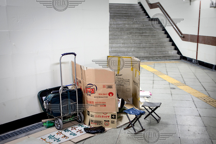 A homeless person sitting in between cardboard in a Seoul subway station.