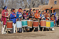 A line of colorfully dressed men drum and sing and during a dance at San Ildefonso Peublo near the village of Pojoque in northern New Mexico