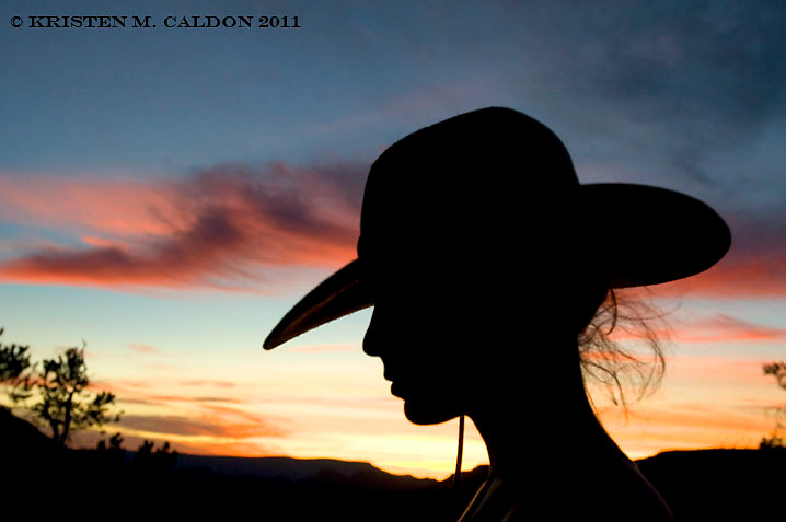 Silhouette of a western woman in cowboy hat with a Arizona sunset.