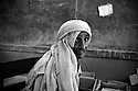 An elderly woman displaced by the floods waits for a consultation with one of the doctors working in the temorary camp housed in the Technical College. Especially children and elderly people are vunerable to many diseases and infections. Karachi, Pakistan, 2010