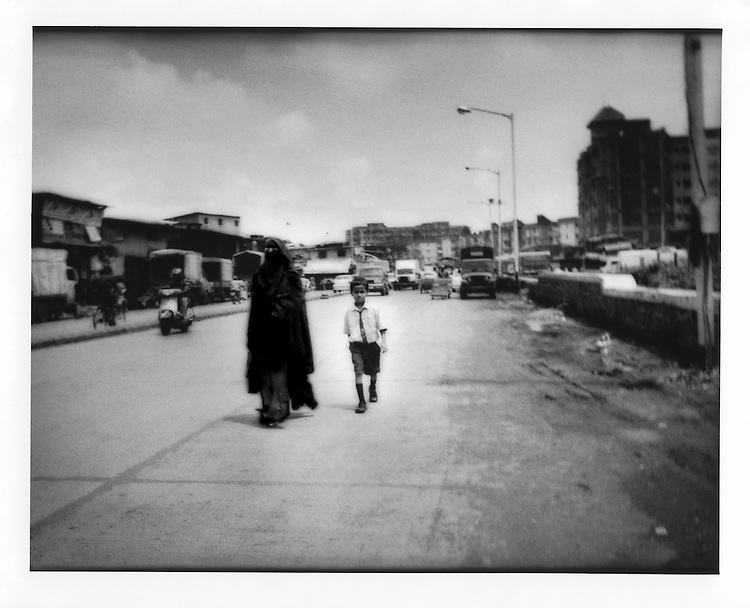 "Mother in ""nijab"", covering her face, walks home from school with her son  in Asia's largest slum, Dharavi, Mumbai, India."