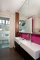 A contemporary London bathroom is equipped with a matching pair of wash basins and bathroom cupboards faced in mirror-glass to maximise the light and space