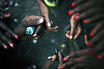 KINSHASA, DEMOCRATIC REPUBLIC OF CONGO - APRIL 30: Esther Yandakwa, age 9, Francine Nyanda, age 14, and Gladys Lutadila, age 14, Clarisse Bongalo, age 14, have their nails done on April 30, 2006 in Matonge district in central Kinshasa, Congo, DRC. They are homeless and work as prostitutes together. They live outside, next to a polluted river. They have all run away from their parents. They have from time to time been living in a homeless shelter for children, but does not like the rules there. They smoke cigarettes, marijuana, drinks whiskey and sometimes take Valium. They charge the clients as little as US$ 1. About 15,000 children are estimated to live on the streets of Kinshasa. Congo is in ruins after forty years of mismanagement by the corrupt dictator and former president Mobuto Sese Seko. He fled the country in 1997 and a civil war started. The country is planning to hold general elections by July 2006, the first democratic elections in forty years.(Photo by Per-Anders Pettersson)
