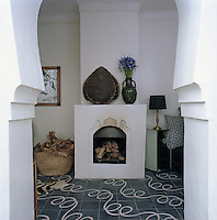 View through an archway into the living room with its open fire and patterned floor tiles by Popham Design