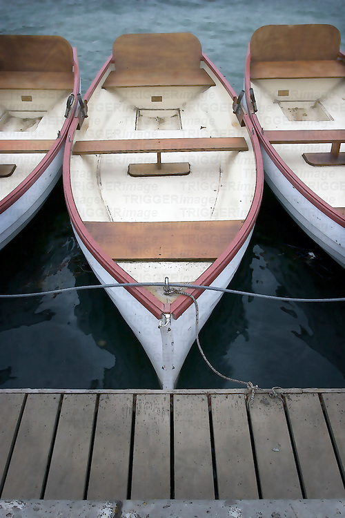 Three rowing boats moored to a jetty
