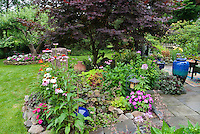 Beautiful colorful backyard and patio, with specimen focal point Japanese maple tree, beautiful ornamental pots and containers, obelisk, raised beds, lawn grass, flowers and foliage plants using annuals and perennials in a lovely mix of tapestry garden design style