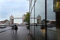 Tower Bridge, 1886-94, by architect Sir Horace Jones and engineer Sir John Wolfe Barry, River Thames, London, UK seen from More London Place. The bascule bridge, symbol of London, is reflected in the glass wall of a modern hotel as well as two pedestrians walking in the evening. Picture by Manuel Cohen