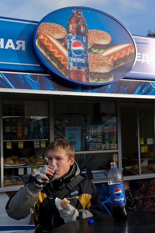 Moscow, Russia, 09/11/2007..Scenes at Pepsi branded kiosks outside Dynamo metro station. Young man eating a pie and drinking Pepsi at a table outside a Pepsi branded hot food kiosk.
