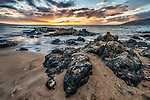 A sunset viewed from the beach over volcanic rocks at Kamaole Beach Park III, Kihei, Maui, Hawaii