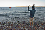 A volunteer waves a refugee boat ashore on a beach near Molyvos, on the Greek island of Lesbos, on November 2, 2015. The boat was provided by Turkish traffickers to whom the refugees paid huge sums to arrive in Greece.