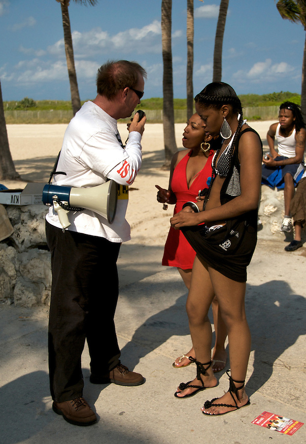A Pastor preaches on the beach while girls argue with him during the  2008 Miami Beach Urban Weekend. The Miami Beach Urban weekend in the largest Urban Festival in the World, that caters toward the Hip Hop Generation. Over 300.000 participants make the annual trek to South Beach for 4 days full of fun, food, festivities, entertainment, music, and more.