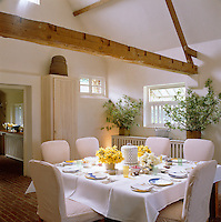 Spring daffodils on the kitchen table laid for lunch with plates designed by Teddy Millington-Drake, painted pails on the window sill filled with willow branches and a straw beehive on top of the tall cupboard