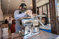 Kris Hofeller wearing a respirator grinds horseradish for the Pickle Guys store in the Lower East Side of New York on Sunday, April 2, 2017. Everyone from millennials to former Lower East Sider's descend on the store to buy the freshly ground pungent horseradish to enjoy and to use in Passover seders. The bitter herb brings tears to our eyes and reminds us of the tribulations afflicted on the Jewish people in their flight from Egypt. Passover begins the evening of April 10.  (© Richard B. Levine)
