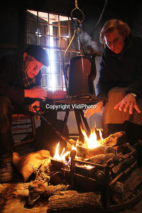 """Foto: VidiPhoto..ARNHEM - Medewerkers van het Nederlands Openluchtmuseum in Arnhem kruipen woensdag dicht bij het houtvuur in een van de boerderijen om zich op te warmen. Het natte en gure weer zorgt er voor dat bezoekers het op dit moment nog laten afweten, ondanks dat het populaire museum vanaf deze week tot en met 15 januari dagelijks open is met """"Kraken of Kwakkelen"""" als thema. Het Arnhemse museum wil de ouderwetse winters laten herleven. Houtkachels, haarden en vuurplaatsen in boerderijen en op het park zorgen in ieder geval voor de nodige sfeer en gezelligheid.."""