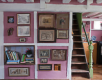 In the living room an entire wall is hung with framed prints which have been found in local antique shops