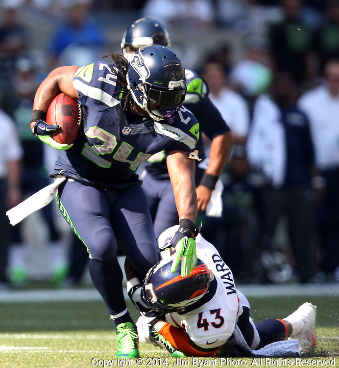 Seattle Seahawks running back Marshawn Lynch (24) fights for extra yardage as he drags Denver Broncos safety T.J.Ward in the second quarter at CenturyLink Field in Seattle, Washington on September 21, 2014.   Lynch ran for 88 yards and scored two touchdowns in the Seahawks 26-20 overtime win over the Broncos.   ©2014. Jim Bryant Photo. All rights Reserved.