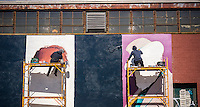 Sign painters paint an advertisement on the side of building in the Williamsburg neighborhood of Brooklyn in New York on Saturday, April 4, 2015.  (© Richard B. Levine)