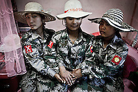 (From left to right) Cobra soldier Seng Ra (21 years old), cobra soldier Pawk Mai (23 years old) and cobra soldier Hka Ra (22 years old) play with fancy hats at their barrack as they are finished their daily duties as trainers of new recruits at the KIA base camp outskirsts of Maiya Jang city, the second largest city under control of the Kachin Independence rebel Army. Since the begining of the Kachin uprising for its sovereignty women always fought by side the rebel soldiers, but officially, the female KIA was founded in 2007, since then, up to 1500 women have joint to the rebel army. The KIA is enhancing its troops number since the ceasefire was broken out by the Burmese army last June 2011.