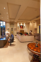 Large living room with wetbar is seen in modern luxury home with very tall ceilings