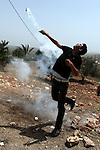 A Palestinian protester throws back a tear gas canister fired by Israeli soldiers during clashes following a protest against the expropriation of Palestinian land by Israel on March 31, 2013 in the village of Kfar Qaddum, near the occupied West Bank city of Nablus. Photo by Issam Rimawi