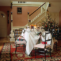 A dining area is set up in the hall of this country house that has been decorated for Christmas