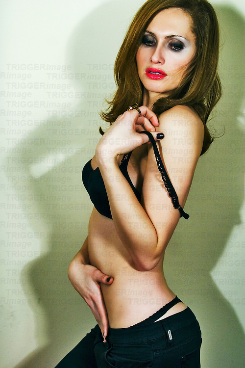A young woman wearing red lipstick removing her bra