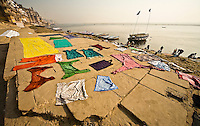 Wet clothes dyed in bright colors are spread out on the ground to dry after being washed in the Ganges.<br /> (Photo by Matt Considine - Images of Asia Collection)